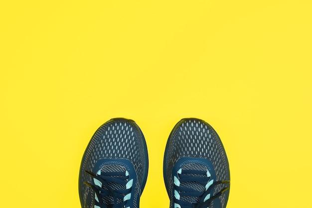 Вид сверху синей спортивной обуви на желтом фоне