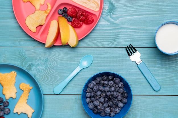 Вид сверху черники и детского питания на тарелке со столовыми приборами