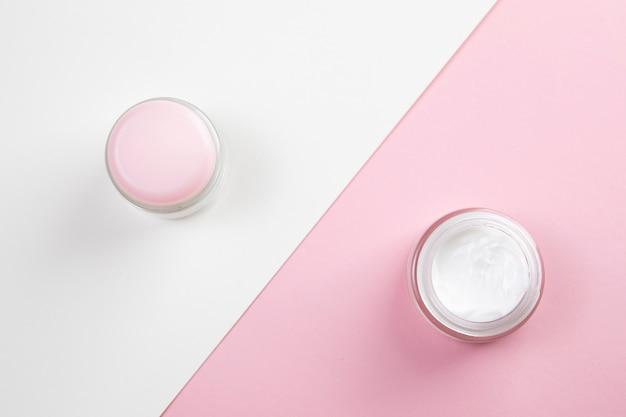 Вид сверху крем для тела на розовом и белом фоне