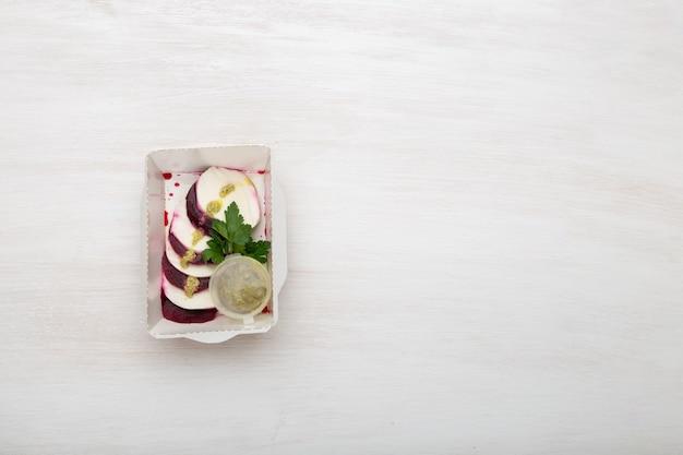 白いチーズのスライスと茹でたビートの上面図は、山羊のチーズの横にある白いテーブルの上にサワークリームソースとパセリが入った白いお弁当箱にあります。プロテインスナックのコンセプト。コピースペース