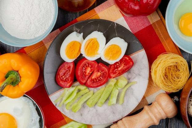 Вид сверху вареных яиц на тарелке с помидорами и ломтиками зеленого болгарского перца на клетчатой скатерти на деревянном фоне