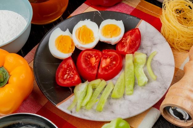 Вид сверху на вареные пополам яйца на тарелке с ломтиками помидоров и болгарского перца на клетчатой скатерти на деревянном фоне