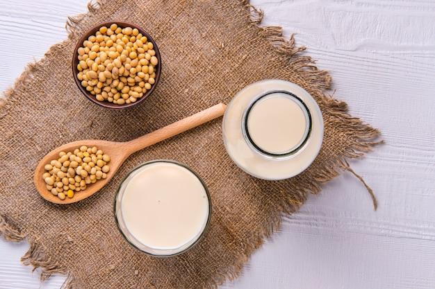Вид сверху бутылка соевого молока с соей на белом столе