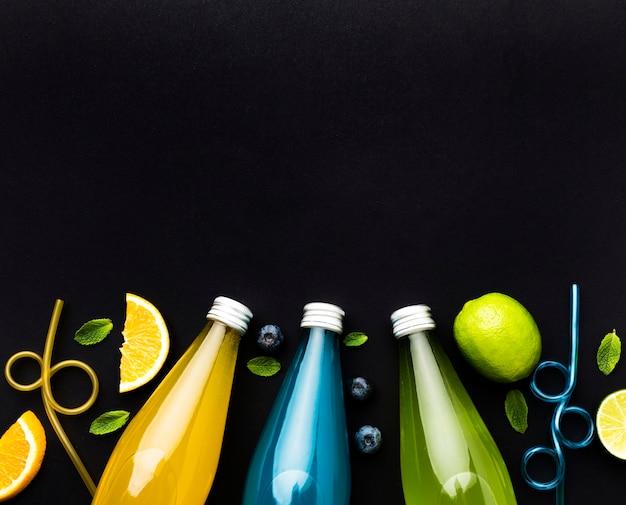 Вид сверху бутылок с безалкогольными напитками и фруктами