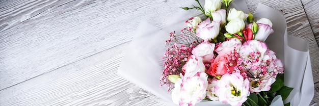 白い木製の背景に花の花束の上面図。テキスト、休日の概念、グリーティングカードのコピースペース。カバー