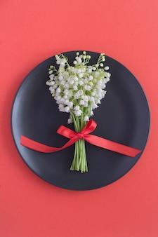 赤い表面の黒いプレート上の谷のユリの花束の上面図。春の花のコンセプト。