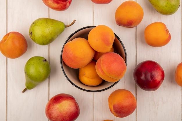 Вид сверху на чашу абрикосов и узор из фруктов в виде персика, абрикоса и груши на деревянном фоне
