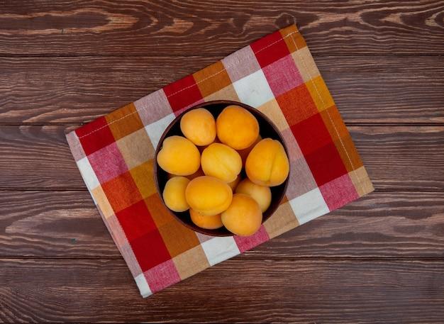 Вид сверху миску абрикосов на ткани и деревянном фоне