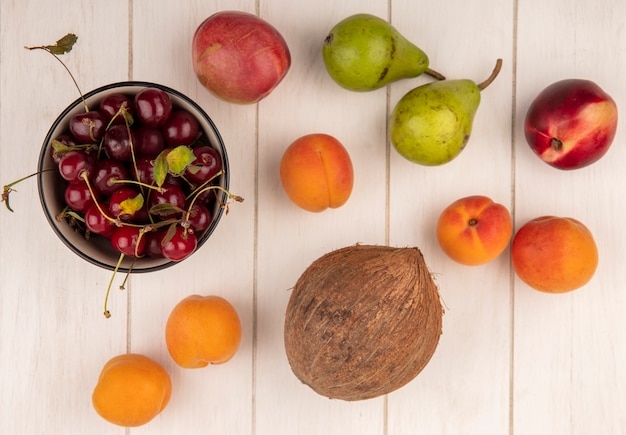 나무 배경에 복숭아 살구 코코넛과 배와 같은 과일의 패턴으로 체리 그릇의 상위 뷰