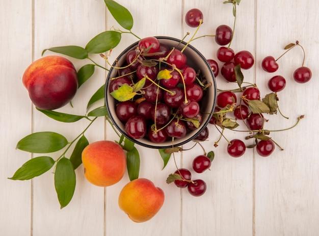 チェリーのボウルと桃とチェリーのパターンの葉の木製の背景の上から見る