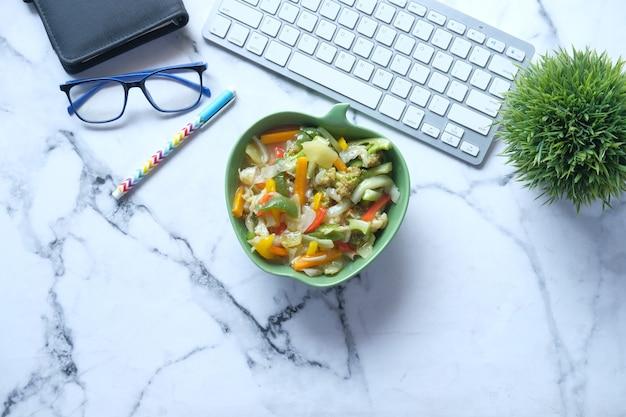 사무실 책상에 신선한 삶은 야채 그릇의 상위 뷰