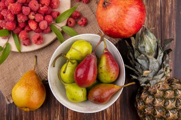 Вид сверху на миску персика и малины на разделочной доске с гранатом и персиком на мешковине и ананасом на дереве