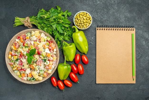 濃い緑色のテーブルの側面に野菜とメモ帳と野菜サラダのボウルの上面図