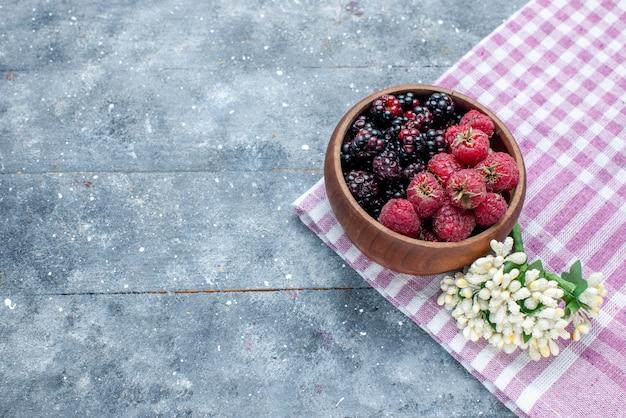 灰色の机の上にベリーの新鮮で熟した果実、ベリーの果実の新鮮な熟したまろやかな森のボウルの上面図