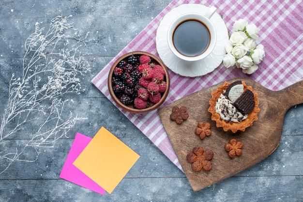 Вид сверху миски с ягодами свежими и спелыми фруктами с кофейным печеньем на сером, ягодном свежем спелом спелом лесу
