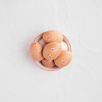 Вид сверху на миску с украшенными пасхальными яйцами