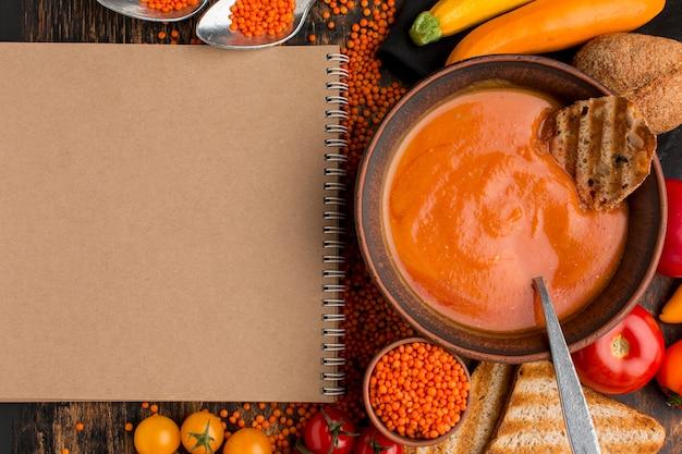 冬カボチャのスープとノートブックとボウルの上面図