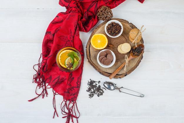 クッキーとクローブのボウル、ハーブティー、赤いスカーフ、白い表面の茶漉しと木の板に柑橘系の果物の上面図