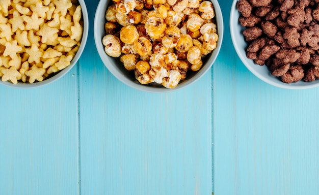 Вид сверху миски различных злаков и сладкий карамельный попкорн на зеленом фоне деревянных с копией пространства