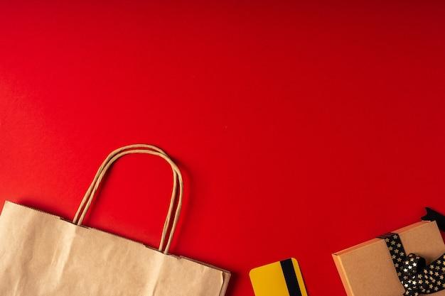 Вид сверху коробки, бумажный пакет и подарок на красном фоне