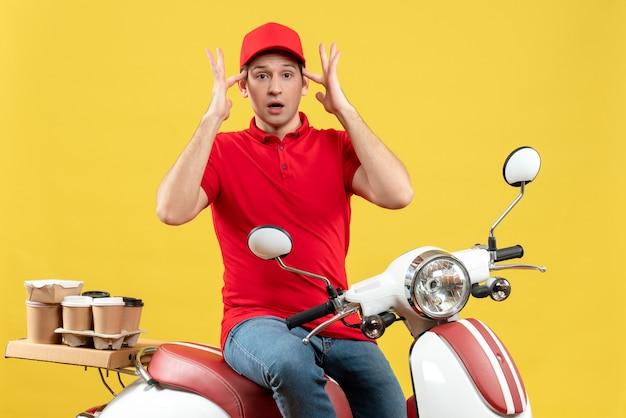 黄色の背景に注文を配信する赤いブラウスと帽子を身に着けている若い男のブレーンストーミングの上面図