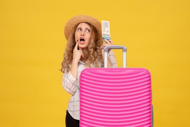 Вид сверху на мозговой штурм молодой леди в шляпе, держащей билет и стоящей за своей розовой сумкой