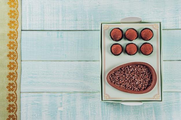 Вид сверху на пасхальное яйцо из бразильского шоколада в подарочной коробке с бразильскими шоколадными конфетами trufas - ovo de chocolate de colher