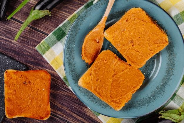 Вид сверху хлебных тостов с баклажанной икрой на тарелке с деревянной ложкой
