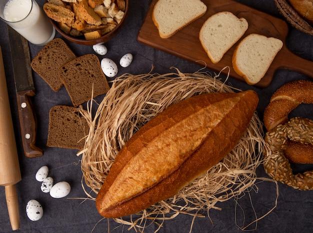 Вид сверху хлеба в виде багета на соломенной ржи и бублика из белого хлеба с молочными яйцами на бордовом фоне