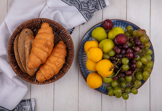 布の上のバスケットと木製の背景のブドウのネクタコットプルオットのプレートのクロワッサンと種をまく茶色の穂軸パンのスライスとしてのパンの上面図