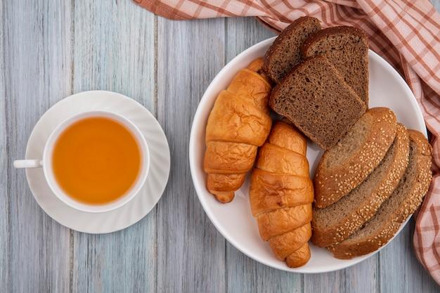 格子縞の布の上のプレートと木製の背景の上の熱いトディのカップのクロワッサンスライスライ麦とシードされた茶色の穂軸としてのパンの上面図