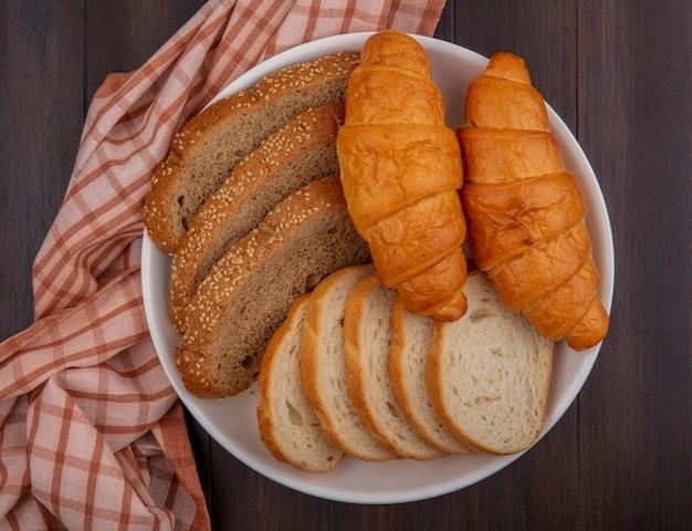 スライスした種をまく茶色の穂軸バゲットと木製の背景の格子縞の布の上のプレートのクロワッサンとしてパンの上面図