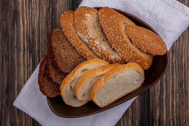 Вид сверху на хлеб в виде нарезанных семенами коричневой ржи и белых хлебов в миске на белой ткани на деревянном фоне
