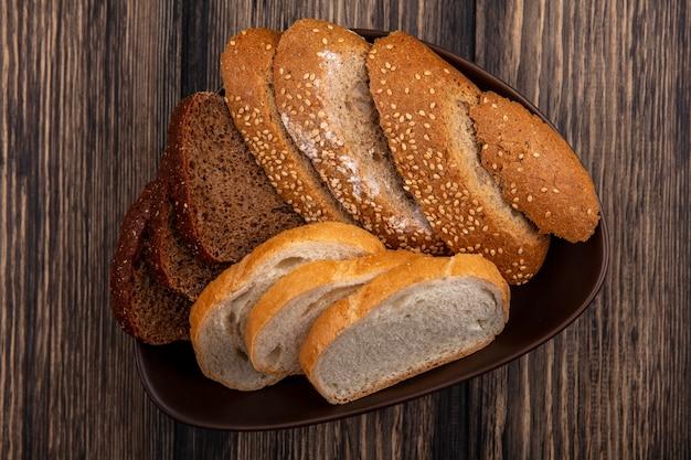 Вид сверху на хлеб, как нарезанный семенами коричневый кочанный ржаной и белый хлеб в миске на деревянном фоне