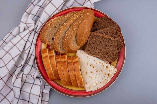 Вид сверху хлеба в виде нарезанного семени коричневого ржаного багета и лепешек в тарелке на клетчатой ткани на сером фоне