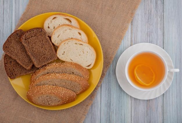 Вид сверху на хлеб в виде нарезанных семенами коричневого ржаного ржаного хлеба в тарелке на вретище и чашке горячего пунша на деревянном фоне