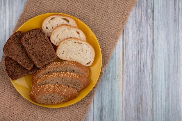 コピースペースと木製の背景の荒布の上のプレートにスライスされたシード茶色の穂軸ライの白いものとしてパンの上面図
