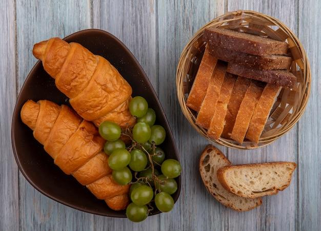 Вид сверху на хлеб круассаны нарезанный ржаной и хрустящими в миске и в корзине с виноградом на деревянном фоне