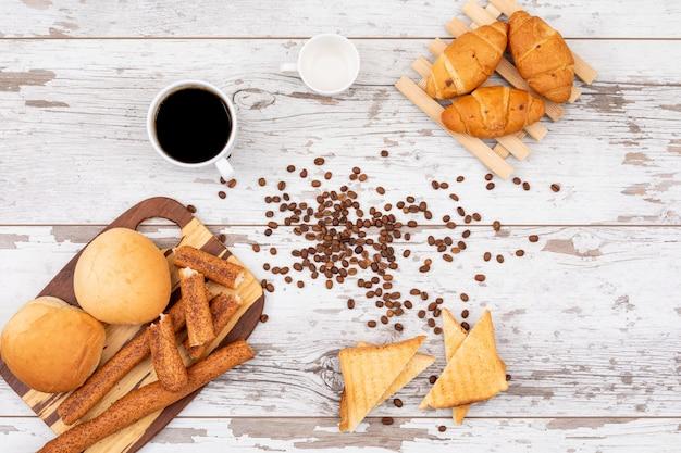 白い木製の表面の水平にコーヒーと朝食パンのトップビュー