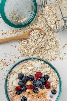 Вид сверху хлопьев для завтрака в миске с фруктами и банкой