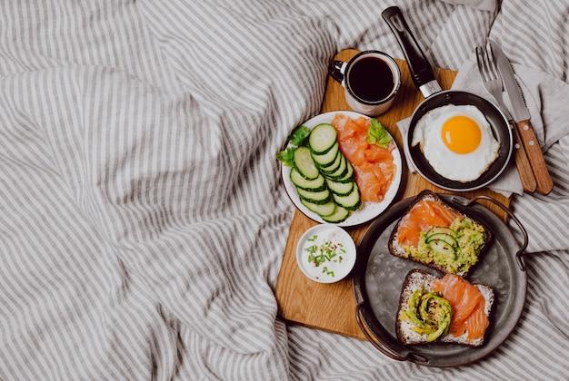 Вид сверху бутербродов для завтрака на кровати с жареным яйцом и тостами с копией пространства