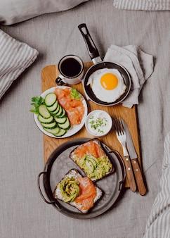 Вид сверху бутербродов на завтрак на кровати с жареным яйцом и тостами