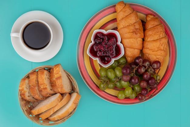 クロワッサングレープラズベリージャムと青い背景の上のお茶とパンのスライスとセットの朝食の上面図
