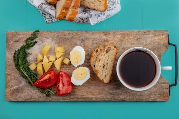まな板の上にお茶と青い背景の上のパンと卵トマトポテトとディルをセットした朝食の上面図