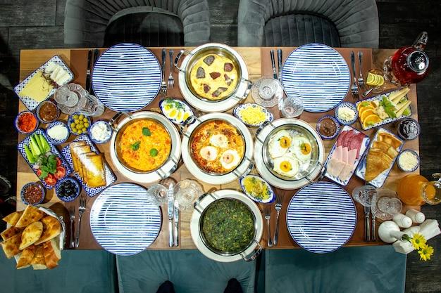 Вид сверху на стол для завтрака плоская кладка яичницы с зеленью помидоров и колбасок