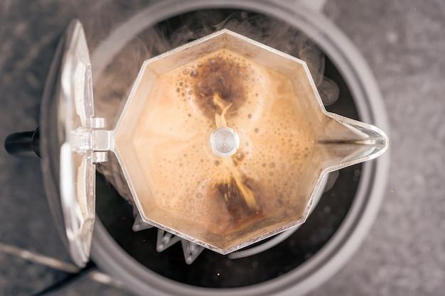 ストーブの上のモカコーヒーポットで新鮮なエスプレッソを醸造する上面図。イタリアの古いスタイル