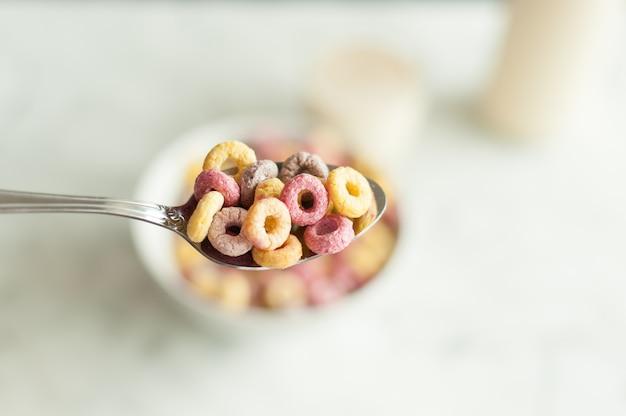 흰색 배경에 숟가락이 있는 그릇에 있는 밝고 다채로운 아침 시리얼의 상위 뷰