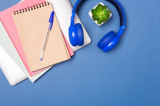 Взгляд сверху яркой красочной столешницы. ноутбук, ноутбук, наушники. работа домашнего офиса. креативность. творческий труд. freelance. стол школьный. скопируйте свободное место.