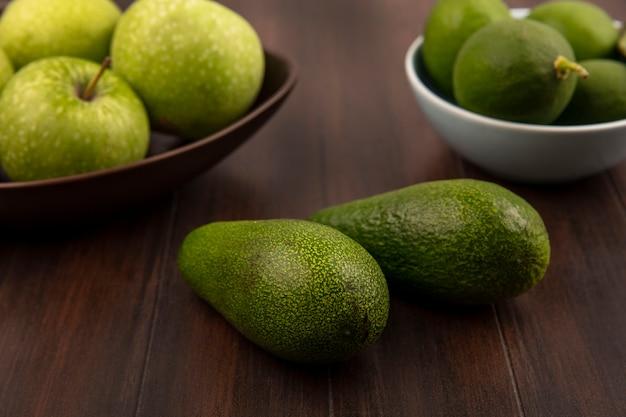 Вид сверху ярко-зеленых авокадо с яблоками на миске с лаймами на миске на деревянной стене