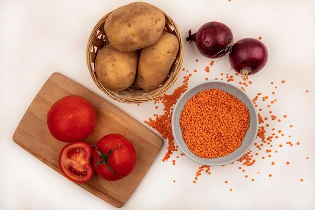 白い壁に分離された赤玉ねぎと木製のキッチンボード上のトマトとバケツの上のジャガイモとボウルの明るいオレンジ色のレンズ豆の上面図